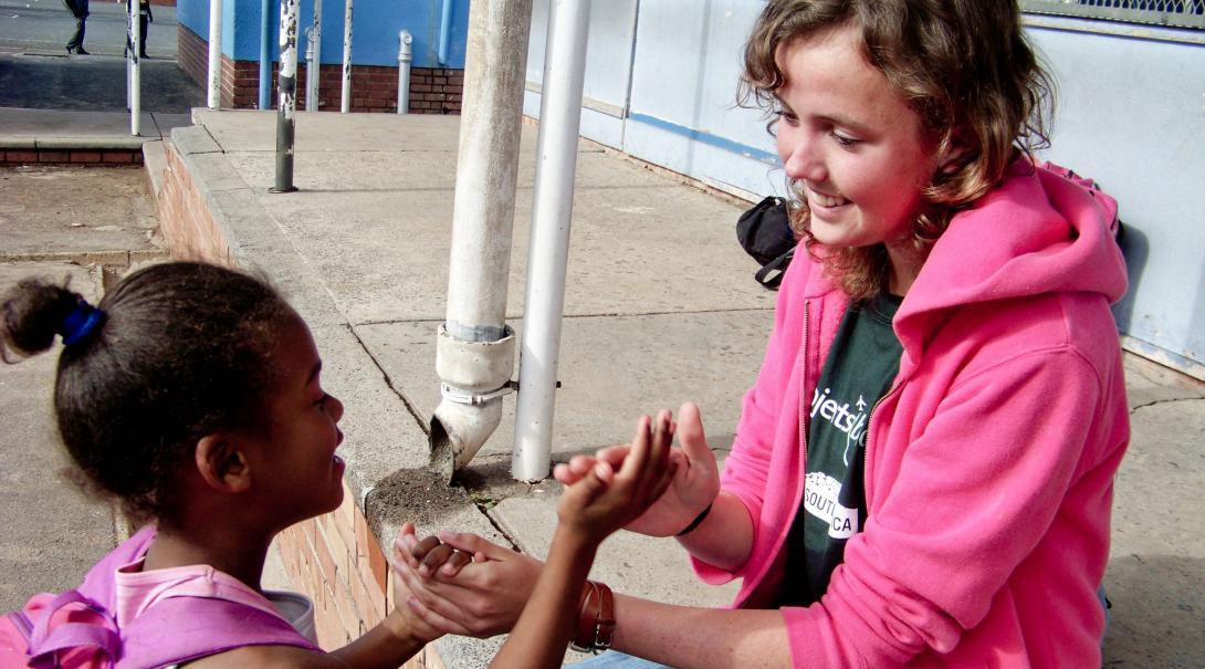 Durante su año sabático antes de la universidad, estudiante juega con niños como parte de su voluntariado social.